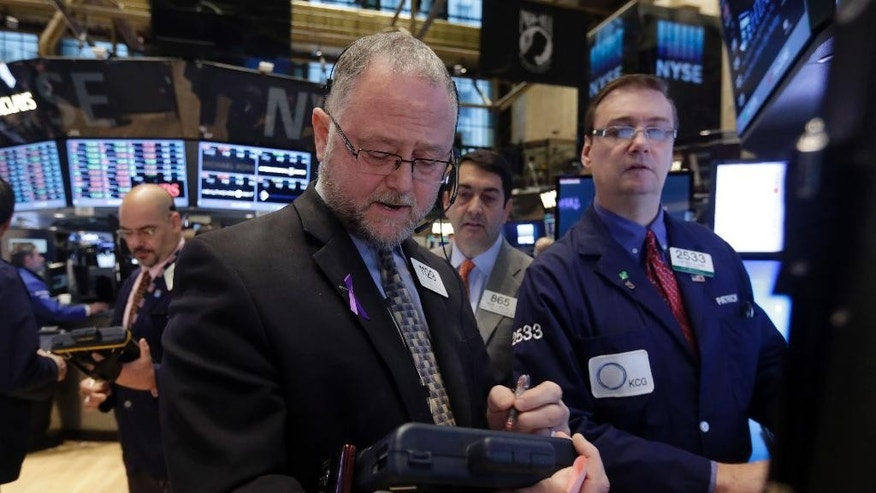 Trader Robert Moran, foreground center, works on the floor of the New York Stock Exchange, Tuesday, Nov. 4, 2014. Stocks edged lower on Tuesday, led by a drop in energy stocks as the price of oil fell to its lowest in four years following reports that Saudi Arabia has cut its prices to the U.S. (AP Photo/Richard Drew)