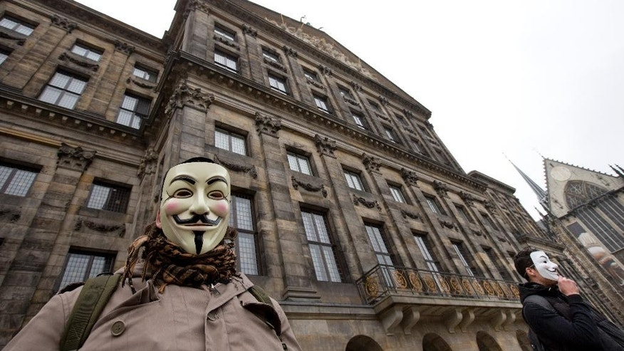 "Demonstrators wear Anonymous masks during a protest rally outside the Royal Palace in Amsterdam, Netherlands, Wednesday, Nov. 5, 2014. If you're caught short on Amsterdam's historic Dam Square, the Dutch government has a message for you: Don't pee on the palace. The stately Royal Palace in downtown Amsterdam is not just a working palace for the Dutch royal family; its dark, sheltered arches are also a favored spot for public urination. After a multimillion-euro renovation ended in late 2011, people began urinating against the palace's sandstone facade. That prompted authorities to put up a fence. But the Interior Ministry on Wednesday called the fence ""unworthy"" of the historic location. It is now installing lights and movement sensors to deter people from relieving themselves.(AP Photo/Peter Dejong)"