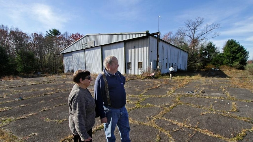 Maureen and Werner Kuesters of Tannersville, Pa., look over the airport hangar and airstrip  at the abandoned Birchwood Resort grounds in Pocono Township, Pa., Tuesday, Nov. 4, 2014,  where where accused Pennsylvania State Trooper killer Eric Frein was arrested last Thursday. Frein evaded capture for 48 days as law enforcement officers combed the wooded countryside. (AP Photo/Scranton Times & Tribune, Michael J. Mullen)  WILKES BARRE TIMES-LEADER OUT; MANDATORY CREDIT