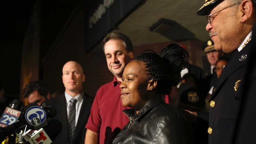 Police officials surround Keisha Gaither, second from right, mother of kidnapping victim Carlesha Freeland-Gaither, following a news conference in Philadelphia on Wednesday, Nov. 5, 2014. Investigators announced Wednesday Carlesha Freeland-Gaither was found in Jessup, Maryland, and the man who took her was arrested. (AP Photo/ Joseph Kaczmarek)