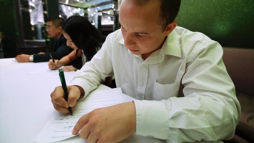 In this Monday, Oct. 6, 2014 photo, Jonathan Alsina, 25, of Miami, fills out paperwork before being interviewed during a job fair at Fontainebleau Miami Beach in Miami Beach, Fla. The Labor Department releases weekly jobless claims for the week of Oct. 27 on Thursday, Nov. 6, 2014. (AP Photo/Wilfredo Lee)