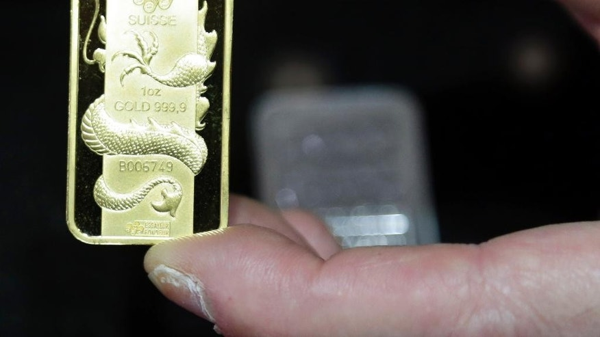 This Wednesday, Nov. 5, 2014 photo shows a Swiss gold coin at Numis International Inc. in Millbrae, Calif. All of the reasons for buying gold over recent years have disappeared, helping to drive prices for the metal to a four-year low. (AP Photo/Marcio Jose Sanchez)