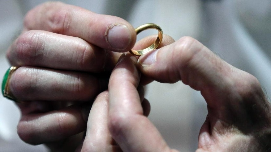 In this Wednesday, Nov. 5, 2014 photo, Numis International Inc. owner Jacob Notowitz examines a gold ring at his store in Millbrae, Calif. All of the reasons for buying gold over recent years have disappeared, helping to drive prices for the metal to a four-year low. (AP Photo/Marcio Jose Sanchez)