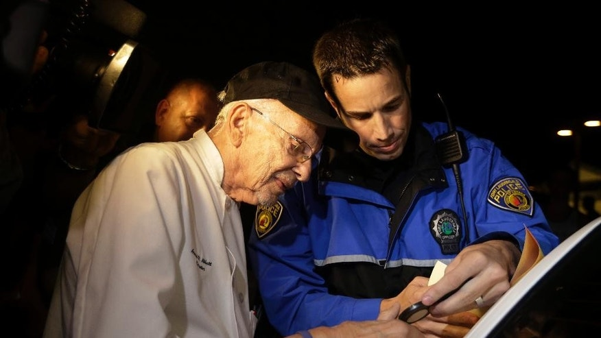 Homeless advocate Arnold Abbott, 90, of the nonprofit group Love Thy Neighbor Inc., left, is fingerprinted by a Fort Lauderdale police officer, Wednesday, Nov. 5, 2014, in Fort Lauderdale, Fla. Abbott and a group of volunteers were feeding the homeless in a public parking lot next to the beach when he was issued a summons to appear in court for violating an ordinance that limits where charitable groups can feed the homeless on public property.  Abbott w also recently arrested along with two pastors for feeding the homeless in a Fort Lauderdale park. (AP Photo/Lynne Sladky)