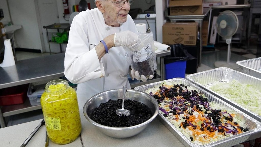 Homeless advocate Arnold Abbott, 90, director of the nonprofit group Love Thy Neighbor Inc., prepares a salad in the kitchen of The Sanctuary Church, Wednesday, Nov. 5, 2014, in Fort Lauderdale, Fla. Abbott was recently arrested along with two pastors for feeding the homeless in a Fort Lauderdale park. Police said they violated a new ordinance that limits where charitable groups can feed the homeless on public property in Fort Lauderdale. Abbott plans to feed the homeless Wednesday in a public parking lot. (AP Photo/Lynne Sladky)