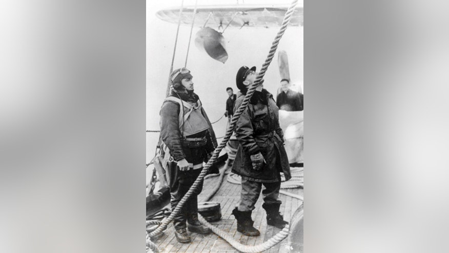 In this 1942 photo released by the U.S. Coast Guard, Lt. John A. Pritchard, Jr., left, waits as his plane is readied aboard a Coast Guard cutter. Pritchard was trying to save a man left stranded by the crash of a B-17 on Greenland's ice cap in 1942 when his own single-engine plane went down in whiteout conditions. The U.S. Coast Guard Academy in New London, Conn, will formally honor Pritchard, a 1938 graduate, on Friday, Nov. 7, 2014, when he will be inducted into its Hall of Heroes. (AP Photo/U.S. Coast Guard)