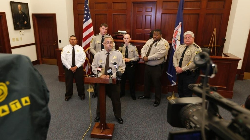 Capt. Jayson Crawley, front at podium, of the Charles City County Sheriff's Office, speaks during a news conference in the county courthouse in Charles City, Va., Thursday, Nov. 6, 2014. Crawley is the lead investigator of the department that led to the arrest of Delvin Barnes, 37, who is being held at a jail in suburban Baltimore County on unrelated charges that he abducted and attempted to kill a 16-year-old Virginia girl. A GPS device installed on the car he was driving led police to capture him in a case involving an abduction in Philadelphia. (AP Photo/Steve Helber)