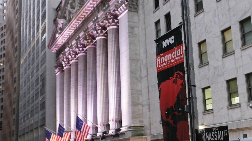 FILE - In this Wednesday, Oct. 8, 2014, file photo, a street sign for Wall Street hangs near the New York Stock Exchange. The government's monthly jobs report fell just short of Wall Street's expectations Friday, Nov. 7, 2014, leaving major stock market indexes to drift in midday trading. (AP Photo/Mark Lennihan, File)