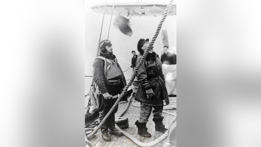 1942 FILE PHOTO of  Lt. John A. Pritchard, Jr., left, as his plane is readied aboard a Coast Guard cutter. Pritchard was trying to save a man left stranded by the crash of a B-17 on Greenlands ice cap in 1942 when his own single-engine plane went down in whiteout conditions. The US Coast Guard Academy in New London, Conn, will formally honor Pritchard, a 1938 grad, Friday, inducting him into its Hall of Heroes.