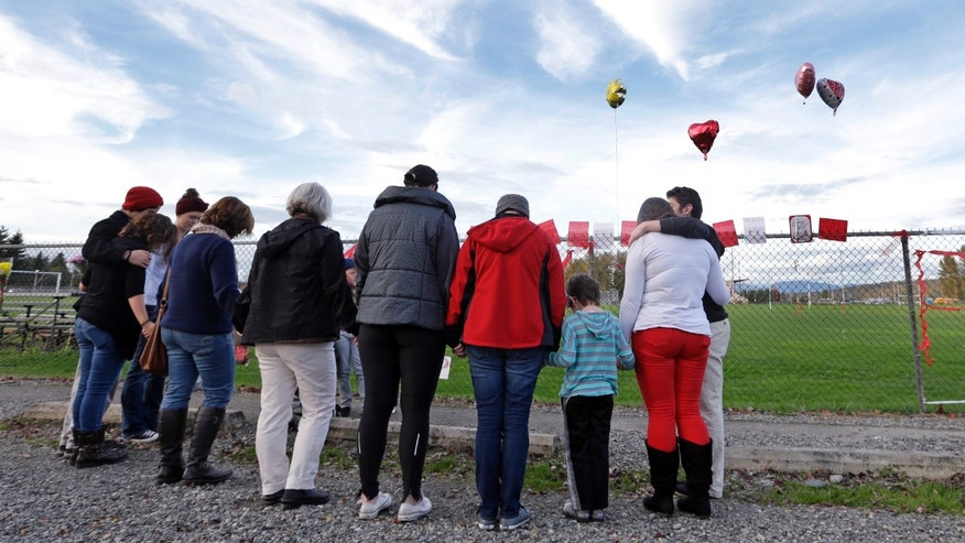 Oct. 29, 2014: People gather in a prayer circle at a fence at Marysville-Pilchuck High School covered with flowers, balloons and messages memorializing a shooting there last week.