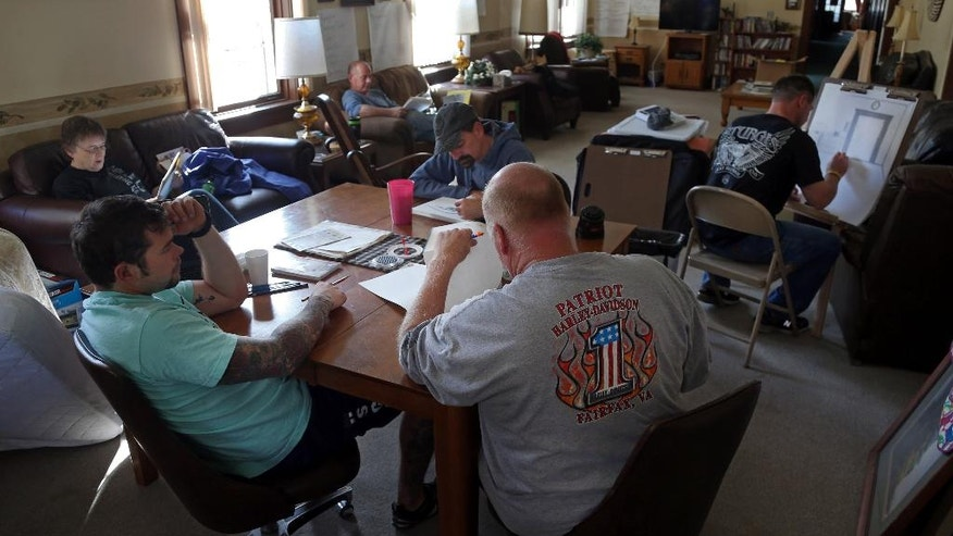 In this Oct. 16, 2014 photo, residents at Eagle's Healing Nest participate in art class  a retreat for veterans, in Sauk Centre, Minn. The retreat provides for veterans who've stumbled in life and are trying to regain their footing. (AP Photo/Jim Mone)