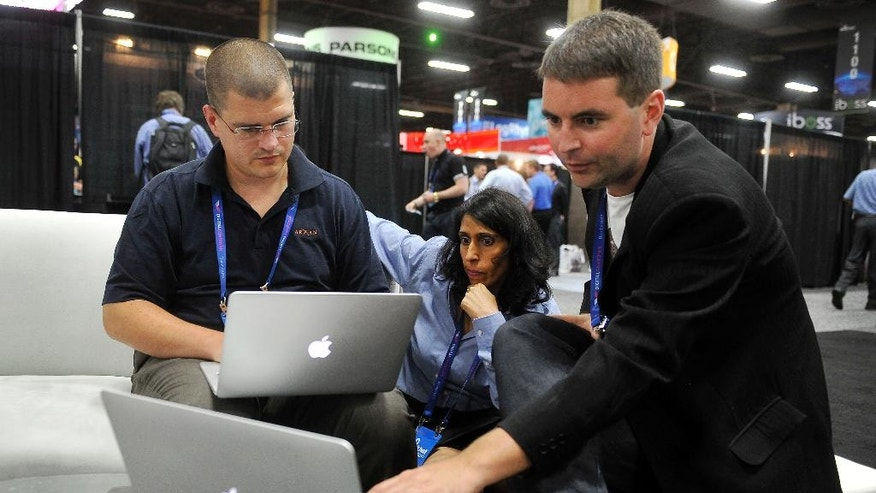 In this Wednesday, Aug. 6, 2014, photo,  Arxan Technologies' Joe Abbey, left, director of software engineering; Jodi Wadhwa, vice president of marketing and Jonathan Carter, technical director, prepare for a hacking demonstration during the Black Hat USA 2014 cyber security conference in Las Vegas. Federal systems grow more susceptible to attack as the government's online offerings expand to user-friendly websites and apps, experts say. (AP Photo/David Becker)