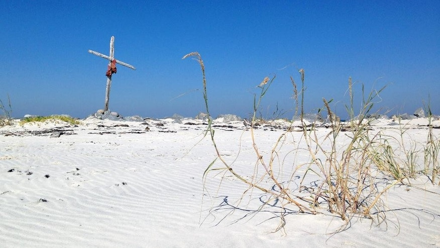A cross and beach grass stand in an area that once was open Gulf water at Dauphin Island, Ala., on Saturday, Oct. 25, 2014. Hurricane Katrina cut the coastal island in two in 2005, but the gash has closed in recent months and the island is whole again because a rock pile created after the BP oil spill in 2010 captured sand washing along the coast. (AP Photo/Jay Reeves)