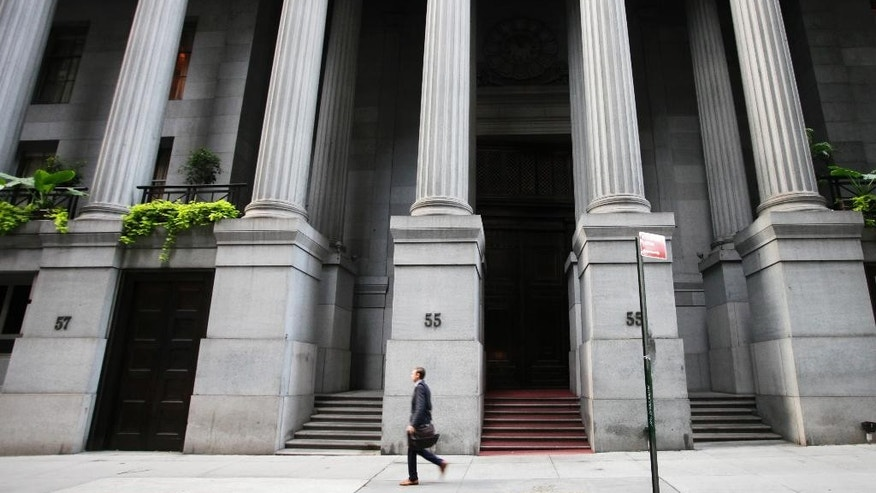 In this Wednesday, Oct. 8, 2014 photo, a man walks to work on Wall Street, in New York. European shares were higher Monday, Nov. 10, 2014, supported by expectations the European Central Bank is prepared to offer new stimulus to nurse the region's recovery. Gains in Asia were spurred by approval of a cross-border trading link between Hong Kong and Shanghai that will give foreigners greater access to Chinese shares. Wall Street looked poised to edge higher. (AP Photo/Mark Lennihan)