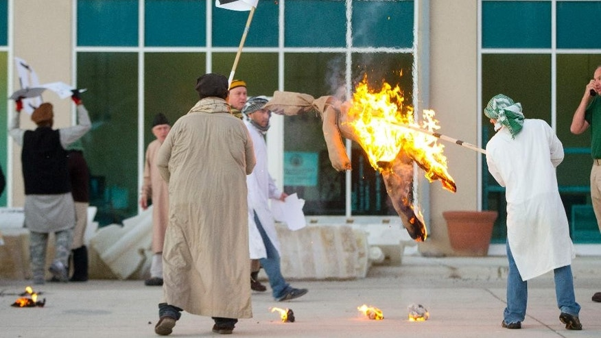 "Participants playing the roles of anti-American demonstrators burn a effigy outside a fake US Consulate during a US Diplomatic Security Service High Threat training program held at a mock town named Erehwon, ""nowhere"" spelled backwards, on a rural Virginia military base, Thursday, Oct. 9, 2014. Two years after the deadly attack on a U.S. facility in Benghazi, Libya, the Diplomatic Security Service that is responsible for protecting some 100,000 Americans around the world has dramatically expanded training.   (AP Photo/Pablo Martinez Monsivais)"