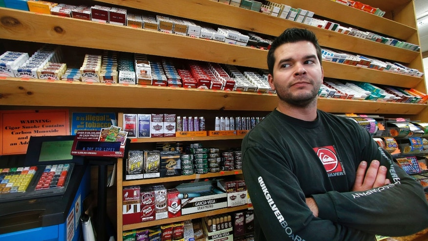 Nov. 6, 2014: Brian Vincent poses in front of a large display of tobacco products at Vincent's Country Store in Westminster, Mass.