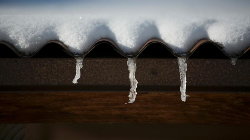 Snow melt from a roof forms into icicles in Bozeman, Mont., Tuesday, Nov. 11, 2014. (AP Photo/Bozeman Daily Chronicle, Adrian Sanchez-Gonzalez)