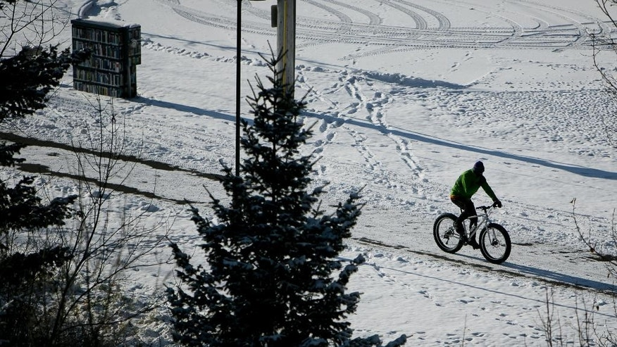 A cyclist, braving the cold temperatures, cruises down on a snow-covered path in Bozeman, Mont., on Tuesday, Nov. 11, 2014. (AP Photo/Bozeman Daily Chronicle, Adrian Sanchez-Gonzalez)