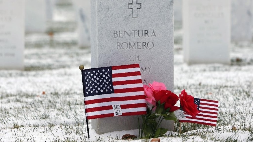 Light snow, American flags, and flowers decorate the grave of U.S. Army Cpl. Bentura Romero at Fort Logan National Cemetery in Sheridan, Colo., on Tuesday, Nov. 11, 2014. A powerful storm made up of the remnants of Typhoon Nuri has moved into the intermountain West, packing high winds and light snow for the region's residents to contend with during the work week. (AP Photo/David Zalubowski)