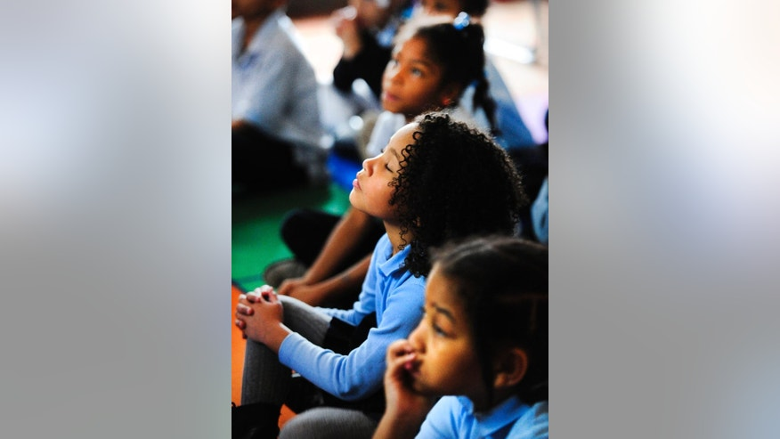 "Mary-Kate Boyles, 7, gets lost in the music during a webcast by the Detroit Symphony Orchestra to students at Yes Academy Wednesday, Nov. 12, 2014, in Detroit.  Boyles sayd, ""This was the first day I've ever heard it.  It was beautiful."" (AP Photo/Detroit News,  Daniel Mears)  DETROIT FREE PRESS OUT; HUFFINGTON POST OUT, MAGS OUT, MANDATORY CREDIT"