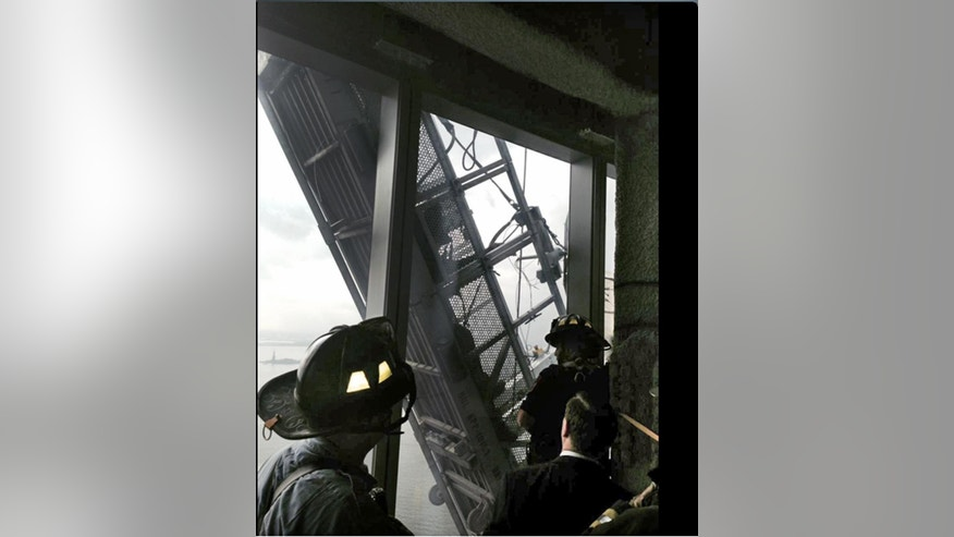 "This photo, from the Fire Dept. of New York Twitter page, shows a window washer's gondola as it hangs from 1 World Trade Center, in New York, Wednesday, Nov. 12, 2014.  Two workers are stuck on scaffolding 69 stories above street level.  A police official, John Miller, says the partially collapsed scaffolding is hanging at ""a 75-degree angle."" The Fire Department said the workers are tethered and communicating with rescuers. (AP Photo/Fire Dept. of New York, Twitter)"