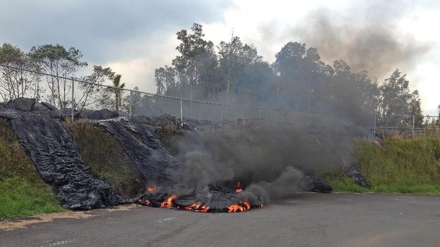 In this photo taken Tuesday, Nov. 11, 2014, and provided by the U.S. Geological Survey, lava flow from the Kilauea Volcano that began on June 27 pushes its way through a fence of a now-closed refuse transfer station and moves down the slope onto station grounds in Pahoa, Hawaii. The flames are caused by burning asphalt. (AP Photo/U.S. Geological Survey)