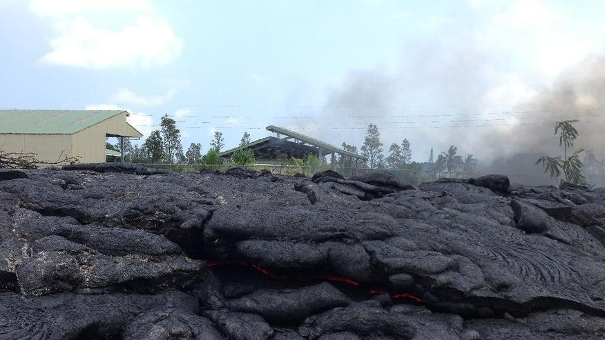 In this photo taken Tuesday, Nov. 11, 2014, and provided by the U.S. Geological Survey, lava flow from the Kilauea Volcano that began on June 27, has inflated up to the level of the now-closed refuse transfer station fence in Pahoa, Hawaii. A glowing crack provides evidence of the flow's molten interior. (AP Photo/U.S. Geological Survey)