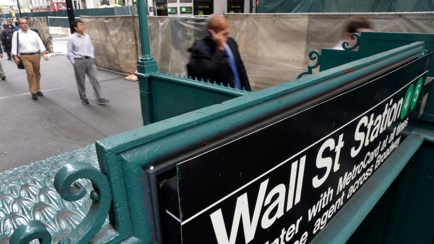 The Wall Street subway stop on Broadway, in New York's Financial District,  Thursday, Oct. 2, 2014. Chinese stocks jumped Wednesday Nov. 12, 2014 after Hong Kong scrapped a daily limit on how much yuan residents can buy as exchanges in both economies prepare for the start of cross border share trading next week.  (AP Photo/Richard Drew)