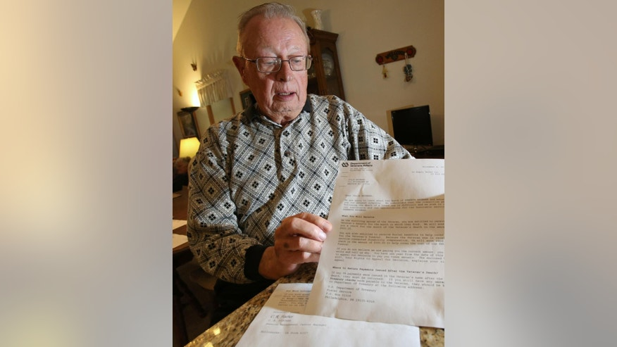 In this photo taken on Tuesday, Nov. 11, 2014, Kenneth C. Brunner, holds up a letter at his home in Madison, Wis., that was addressed to his wife from the Department of Veterans Affairs stating that he had died and she would receive a check for the month that he passed. Brunner, an 81-year-old Army veteran, says he tried to call the agency Tuesday to deliver a few choice words, but the office was closed for Veterans Day. (AP Photo/Wisconsin State Journal, Amber Arnold)