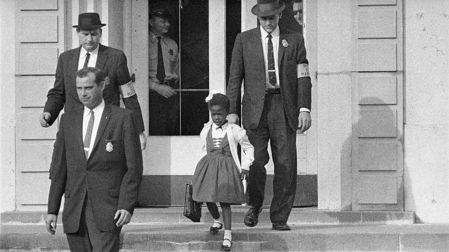 FILE - U.S. Deputy Marshals escort 6-year-old Ruby Bridges from William Frantz Elementary School in New Orleans, in this November 1960, file photo. On Friday, Nov. 14, 2014, 54 years later to the day when she first walked up the steps to the school, Bridges is scheduled to commemorate the event with the unveiling of a statue in her likeness on the campus. (AP Photo/File)