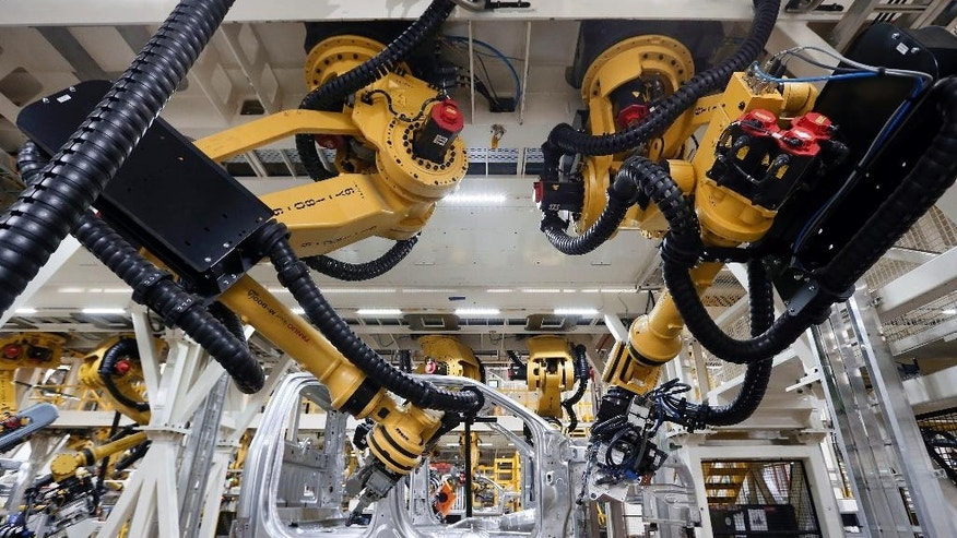 In this Nov. 11, 2014 photo, robots install rivets on a 2015 Ford F-150 truck at the Dearborn Truck Plant in Dearborn, Mich., Tuesday, Nov. 11, 2014. The Commerce Department releases business inventories for September on Friday, Nov. 14, 2014. (AP Photo/Paul Sancya)