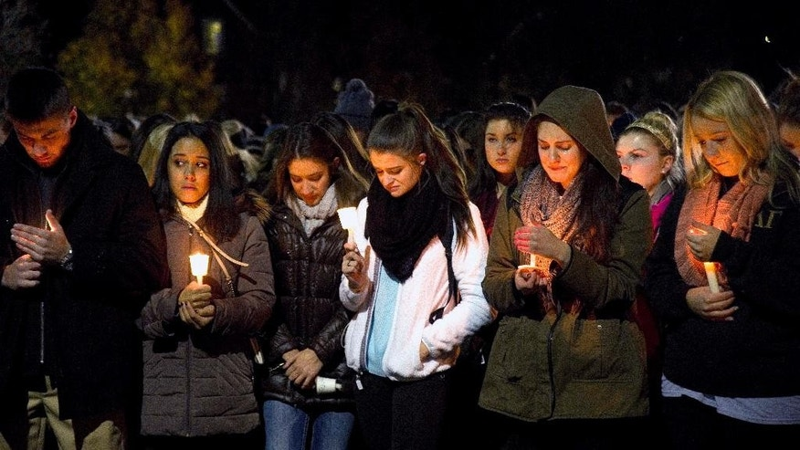 West Virginia Univeristy students hold a candlelight vigil in memory of Nolan Michael Burch in Morgantown, W.Va., Friday, Nov. 14, 2014, after Burch died Friday. Burch, 18, died two days after officers were called to the Kappa Sigma house and found someone performing CPR on him. (AP Photo/The Dominion-Post, Josh Young)