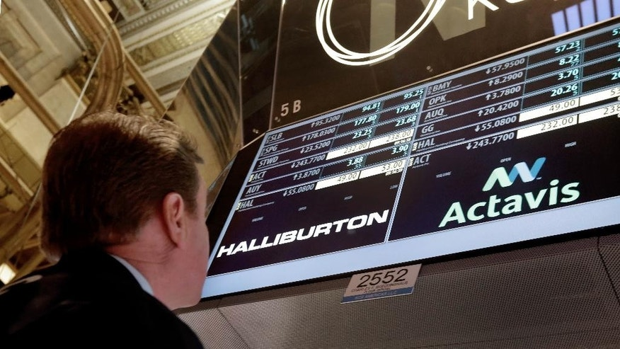 Specialist Michael O'Mara looks at the board at his post on the trading floor of the New York Stock Exchange Monday, Nov. 17, 2014. Allergan has reached a friendly deal to be acquired by Actavis PLC in a deal valued at $66 billion, while Halliburton is buying rival oilfield services company Baker Hughes in a cash-and-stock deal worth $34.6 billion. (AP Photo/Richard Drew)