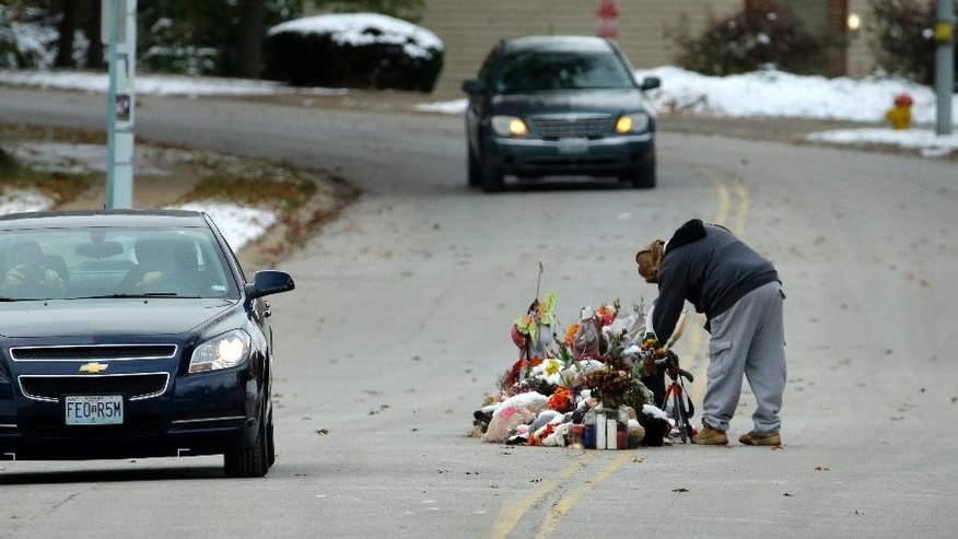 A woman looks at a memorial in the middle of the street Monday, Nov. 17, 2014, more than three months after black teen Michael Brown was shot and killed there by a white policeman in Ferguson, Mo. The shooting sparked weeks of violent protests and  Missouri Governor Jay Nixon declaring a state of emergency today as a grand jury deliberates on whether to charge Ferguson police officer Darren Wilson in the death. (AP Photo/Charlie Riedel)