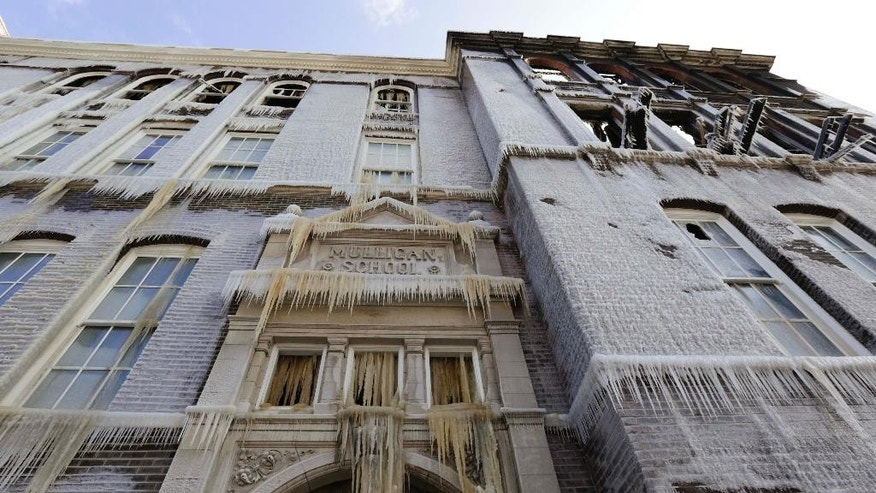 An entrance at the former Mulligan Elementary School in Chicago is seen caked in ice Wednesday, Nov. 19, 2014, one day after a fire gutted the 114-year-old building, which developers had planned building into condominiums. The water used by firefighters quickly froze, leaving icicles hanging from the school's exterior. (AP Photo/Teresa Crawford)