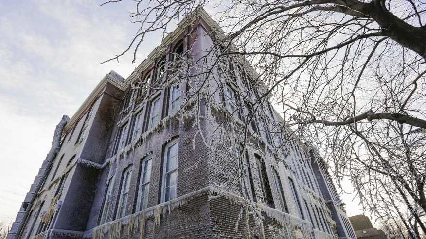 The former Mulligan Elementary School in Chicago is seen caked in ice Wednesday, Nov. 19, 2014, one day after a fire gutted the 114-year-old building, which developers had planned building into condominiums. The water used by firefighters quickly froze, leaving icicles hanging from the school's exterior. (AP Photo/Teresa Crawford)