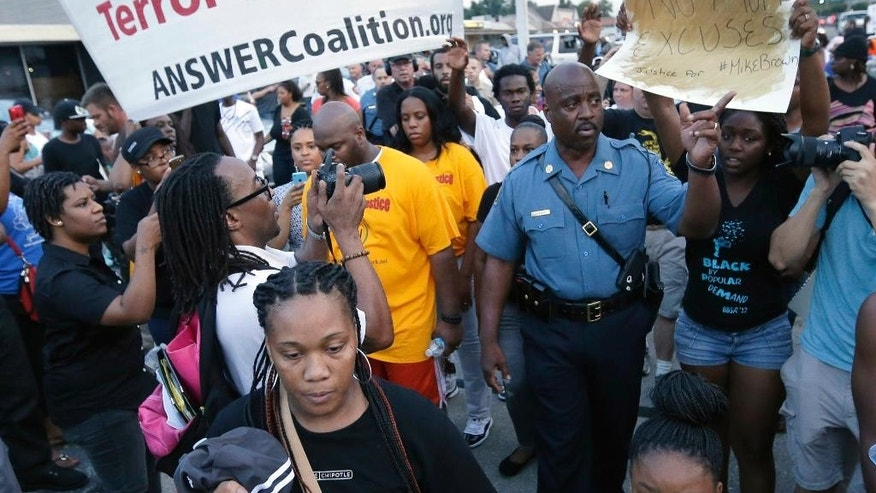 FILE - In this Aug, 16, 2014 file photo Missouri Highway Patrol Capt. Ron Johnson, center right, walks among people protesting the police shooting death of Michael Brown in Ferguson, Mo. Emails sent to top public-safety officials both criticizing and praising Johnson for appearing to sympathize with protesters illustrate one of the challenges that authorities could face after a grand jury decides whether to charge the police officer who killed Brown _ how to walk a fine line between providing public empathy and security. (AP Photo/Charlie Riedel, File)