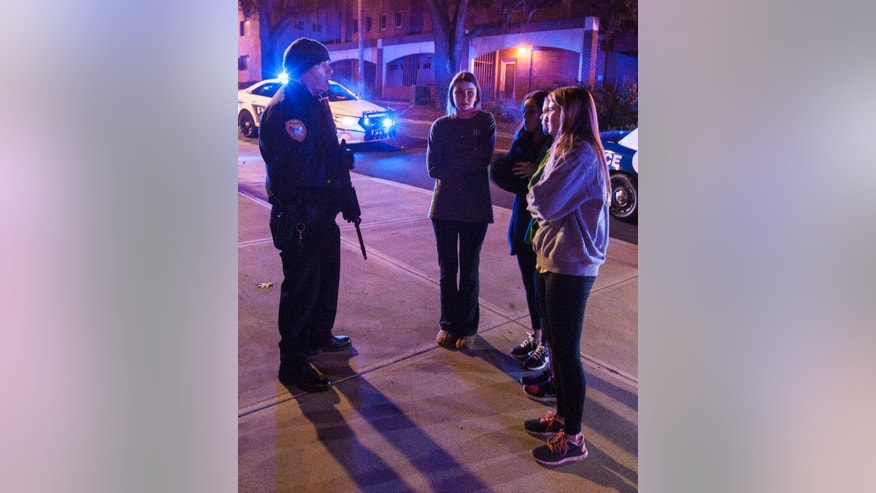 A Tallahassee police officer talks to several students outside the Strozier Library on the Florida State University campus in Tallahassee, Fla., where a shooting occurred early Thursday, Nov 20, 2014. The gunman was shot and killed by police officers. (AP Photo/Mark Wallheiser)