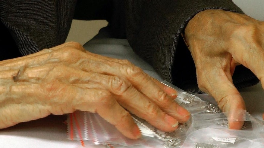 In a Tuesday, Nov. 18, 2014 image from video, Frances Moore, 93, sorts bags of necklaces at Bromberg & Co. jewelry in Mountain Brook, Ala. Moore, who has worked for the company for 75 years, is the longest-tenured employee ever at a family-owned company that dates to 1836. (AP Photo/Jay Reeves)