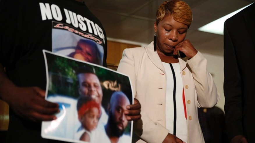 Aug. 11, 2014: Lesley McSpadden, the mother of 18-year-old Michael Brown, wipes away tears as Brown's father, Michael Brown Sr., holds up a family picture of himself, his son, top left, and a young child during a news conference in Jennings, Mo. (AP/Jeff Roberson, File)