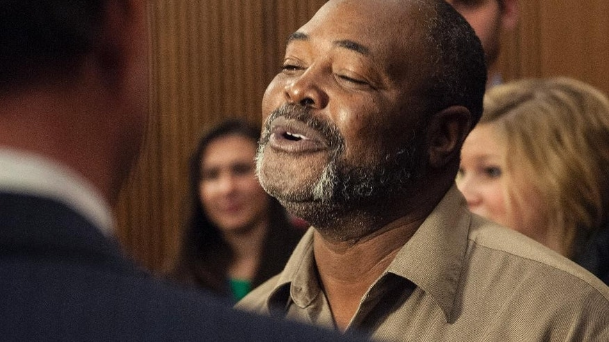 Kwame Ajamu of Cleveland reacts after the life sentence of Ricky Jackson, also of Cleveland,  for a 1975 murder was ended by Cuyahoga County Common Pleas Judge Richard McMonagle, Friday, Nov. 20, 2014 in Cleveland. Ajamu was also convicted for the same murder but had been previously released. The sentence was dismissed after the main witness recanted his testimony. (AP Photo/Phil Long)