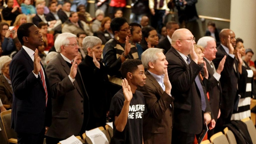 Members of a 16-member Ferguson Commission are sworn in by Missouri Gov. Jay Nixon Tuesday, Nov. 18, 2014, in St. Louis. The independent commission has been created to study issues that have surfaced since the fatal police shooting of Michael Brown. (AP Photo/Jeff Roberson)