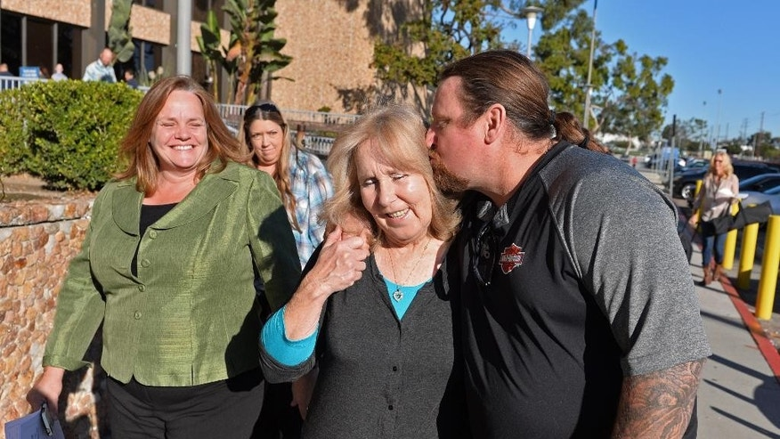 David Mellen, kisses his aunt, Susan Mellen, after they leave Torrance Superior Court where she was declared factually innocent for a murder she spent 17 years in prison for, Friday, Nov. 21, 2014, in Torrance, Calif. Judge Mark Arnold made the ruling Friday in Los Angeles County Superior Court. Arnold previously overturned Mellen's conviction in the 1997 beating death of a homeless man. Her conviction was based on the testimony of a notorious liar. Prosecutors agreed Mellen was wrongly convicted.  (AP Photo/The Daily Breeze, Brad Graverson)  MAGS OUT; NO SALES