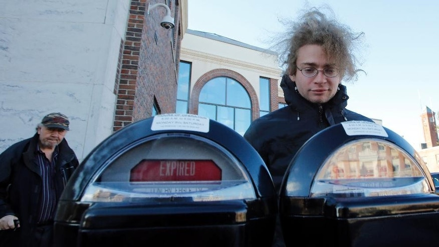 "In this photo taken Wednesday Nov. 19, 2014, one of many self-proclaimed ""Robin Hooders"" Garret Ean puts money in expired meters ahead of parking enforcement officers on Main St. in Keene, N.H. A merry band of Keene activists stalk  parking enforcement officers, pumping quarters into expired meters before the officers write tickets. But city officials say their practice of taunting and videotaping the officers interferes with their work and stresses them out. The New Hampshire Supreme Court is deliberating if there is a line to be drawn between constitutionally-protected free speech rights and protecting government employees from harassment.  (AP Photo/Jim Cole)"