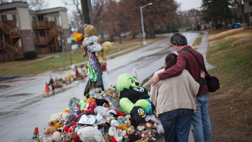 Lisa Tebbe, left, embraces her husband John Powell, both of Ferguson, Mo., while looking over the sidewalk memorial near the spot where Michael Brown was shot and killed more than three months ago, Saturday, Nov. 22, 2014, in Ferguson, Mo. Ferguson and the St. Louis region are on edge in anticipation of the announcement by a grand jury whether to criminally charge Officer Darren Wilson in the killing of 18-year-old Michael Brown. (AP Photo/David Goldman)