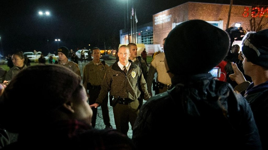 Police warn protesters to stay out of the street or face arrest during a demonstration outside the Ferguson Police Department, Sunday, Nov. 23, 2014, in Ferguson, Mo. Ferguson and the St. Louis region are on edge in anticipation of the announcement by a grand jury whether to criminally charge Officer Darren Wilson in the killing of 18-year-old Michael Brown. (AP Photo/David Goldman)