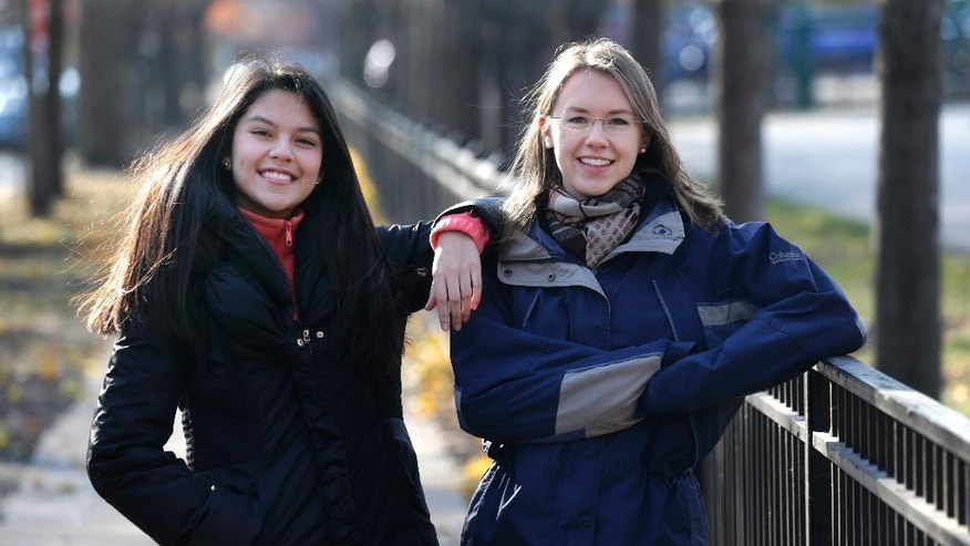 In this Nov. 19, 2014 photo, Lakeview High School teacher Kristin Hu, right, who attends the LaSalle Street Church, poses for a portrait with student Lucy, outside the school in Chicago. In September, members and regulars at the church each received $500 checks from the church. Hu plans to give $500 to a Dreamer organization or start a scholarship foundation for the kids. Lucy, a Mexican-born Dreamer in her class, inspired Hu after she spoke of how she and others want to attend college but don't qualify for financial aid because of their immigration status. (AP Photo/Charles Rex Arbogast)