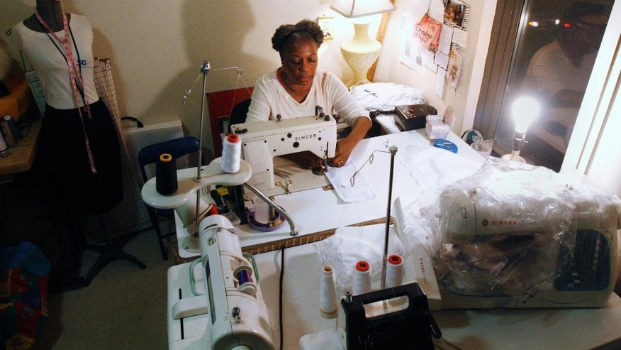 In this Nov. 4, 2014 photo, Jeliner Jordan, 71, sews at her apartment in Chicago. In September, Jordan and other members and regulars at the Lasalle Street Church in Chicago each received a $500 check from the church with the instruction that they were to do what they felt called to do with the money, which represented 10 percent of the profit from the sale of some land the church co-owned. (AP Photo/Martha Irvine)
