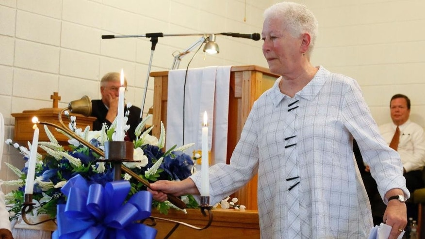 "In this June 15, 2014 photo, Rita Schwerner Bender, widow of Michael Schwerner, lights a candle during a commemorative service for her husband and the two other men killed in the ""Mississippi Burning"" case, at Mt. Zion United Methodist Church in Philadelphia, Miss. Michael Schwerner, Andrew Goodman and James Chaney are going to be posthumously awarded the Presidential Medal of Freedom on Monday, Nov. 24, 2014, but the honor is not sitting well with some of their relatives. (AP Photo/Rogelio V. Solis, File)"