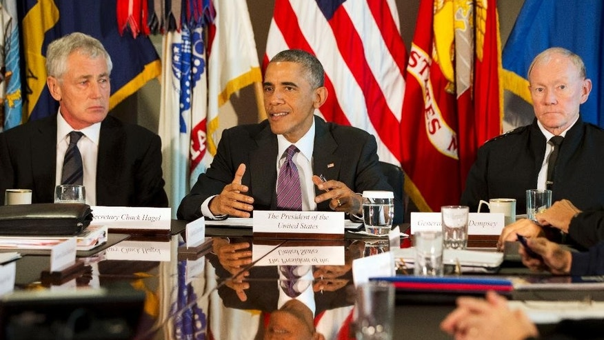 FILE - In this Oct. 8, 2014 file photo, President Barack Obama, flanked by Defense Secretary Chuck Hagel, left, and Joint Chiefs Chairman Gen. Martin Dempsey, speaks to the media at the conclusion of a meeting with senior military leadership, at the Pentagon. Defense Secretary Hagel is resigning from the Obama Cabinet Monday. (AP Photo/Jacquelyn Martin)